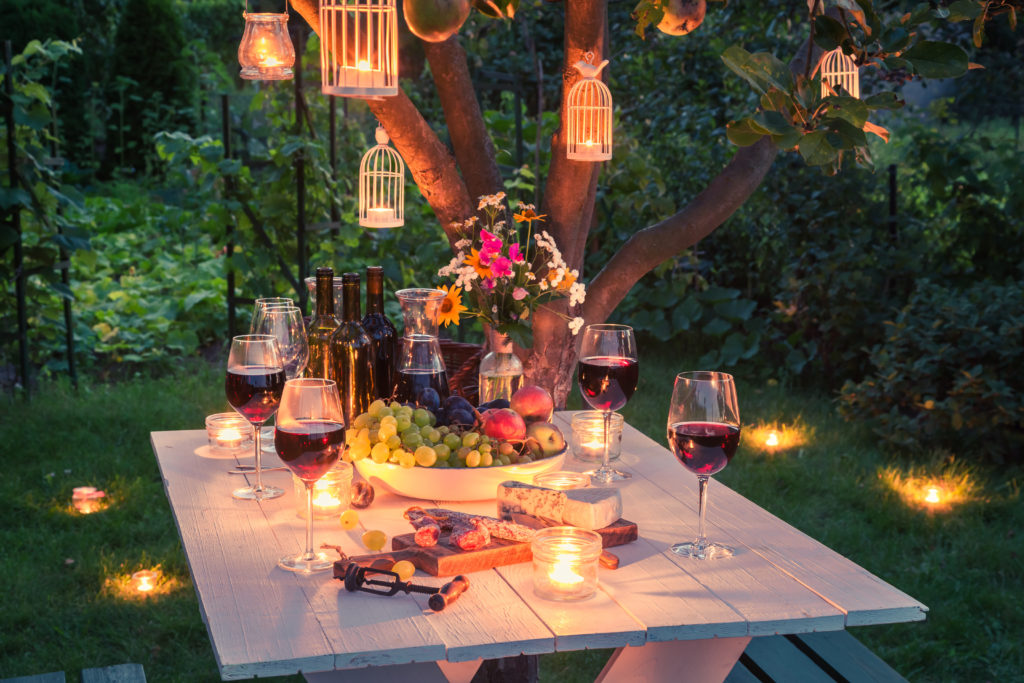 outdoor picnic table loaded for a party with the right electrical lighting around it for ambiance