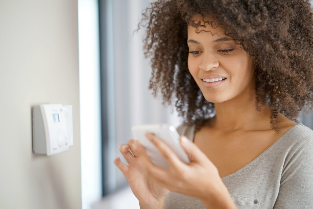 Woman controlling home temperature with electronic device