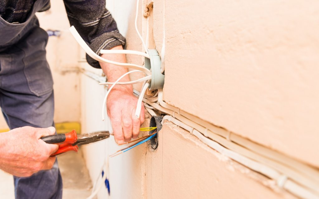 man working with pliers at house wall wires