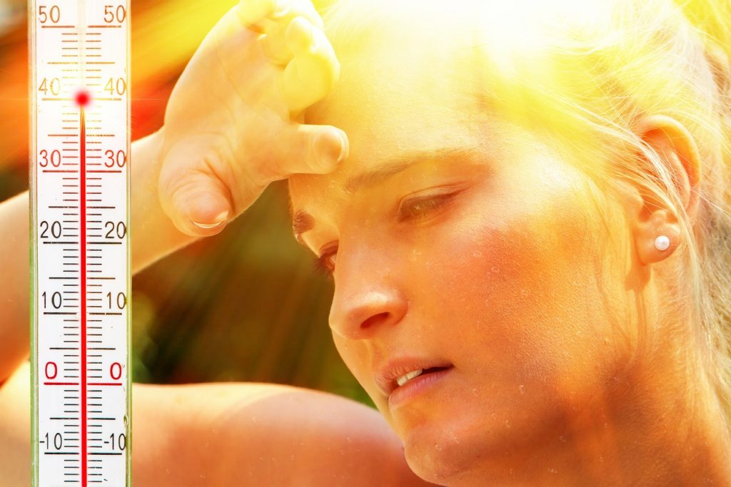 woman enduring hot temperatures with a thermometer next to her