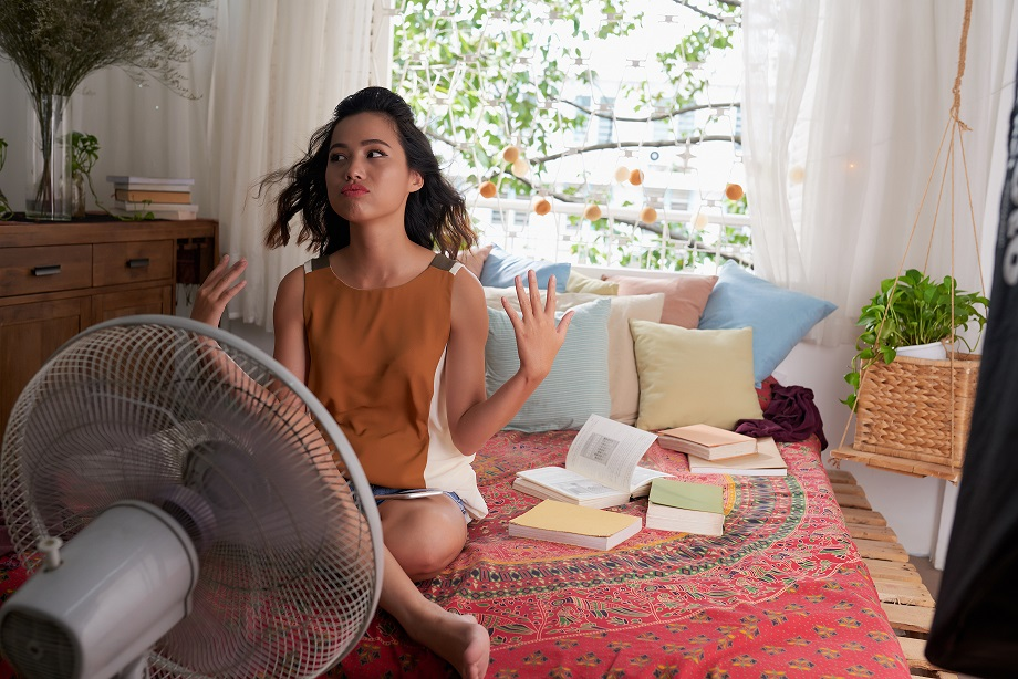 Asian girl in front of fan, thinking about calling air conditioning services to beat the heat.
