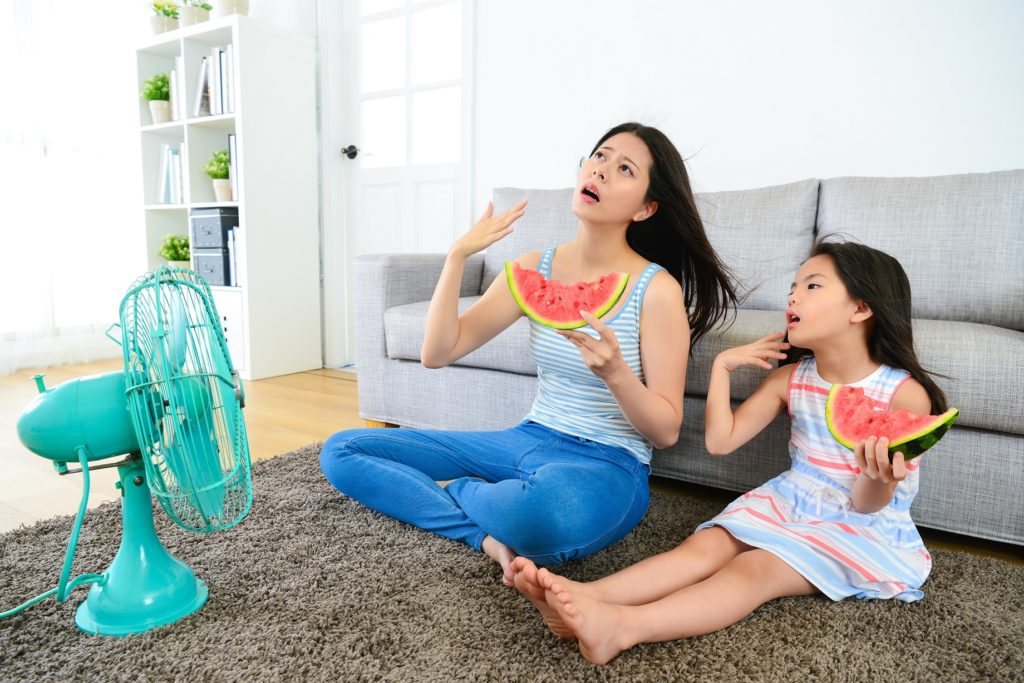 Woman and daughter sitting in front of fan, trying to keep cool while eating watermelon as woman considers converting to refrigerated air