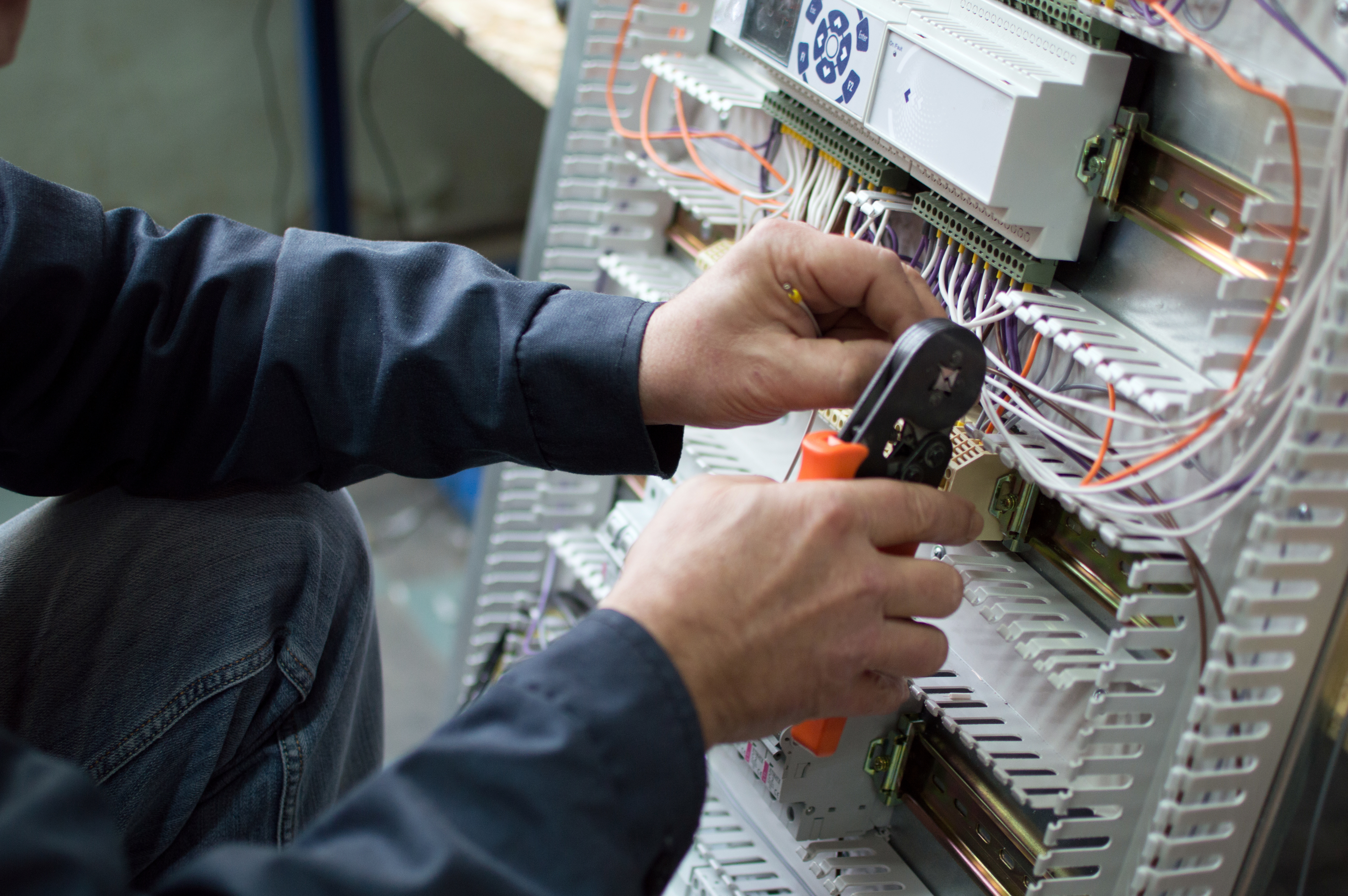 Electrician assembling industrial control cubicle in workshop.